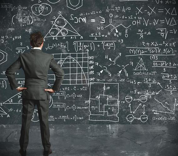 man-looking-at-formulas-and-numbers-on-chalkboard