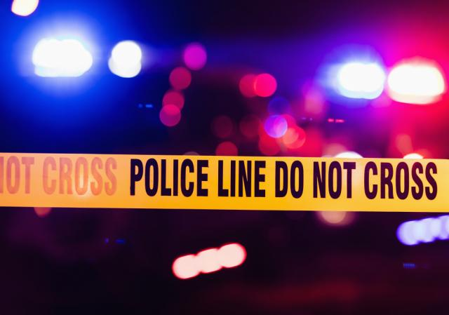Accident or crime scene cordon tape, police line do not cross. It is nighttime, emergency lights of police cars flashing blue, red and white in the background|640x449.53674508852777